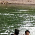 Shinichi Asao swimming in crocodile infested river at La Selva Biological Station, Costa Rica