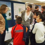 Elementary students investigating posters with GDPE graduate student
