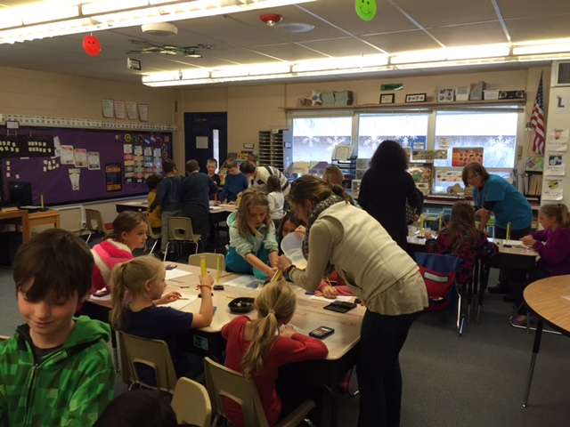 Teachers working with elementary students on science project