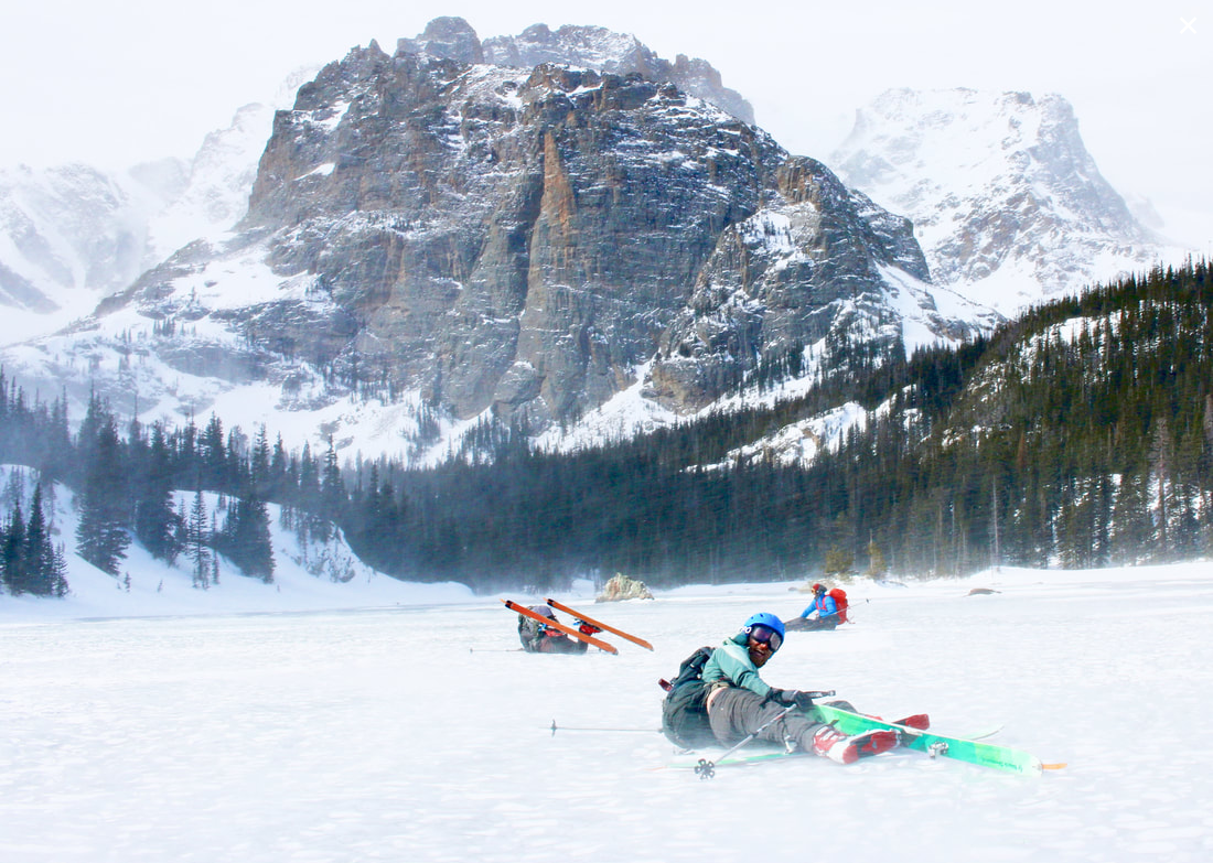 skiers splayed out on lake ice, blown over by wind
