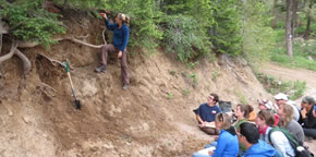 SSI student observing layers of exposed mountain soils